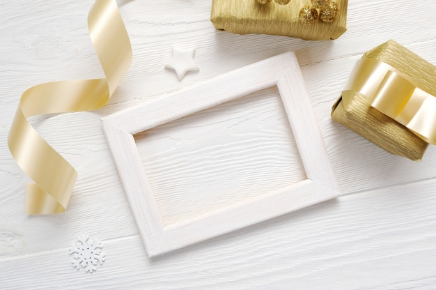 Mockup christmas white frame with a golden ribbon and a gift