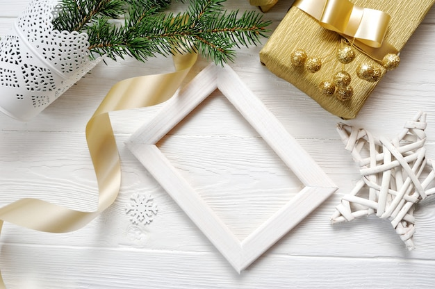 Mockup christmas white frame with tree and golden ribbon and a gift