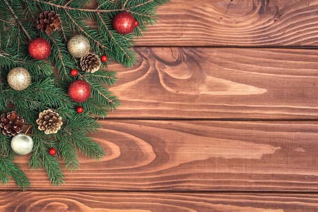 Mockup of christmas wooden rustic vintage background with fir branches, pine cones, red and golden balls. christmas frame, decorations. flat lay. copy space.