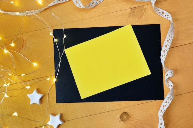 Mockup christmas yellow sheet of paper box with xmas garland on golden wooden background.