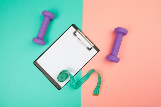 Mockup clipboard with gym equipment dumbbell on blue and pink