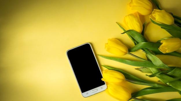 カラフルな黄色の背景のパノラマ写真の上面図にチューリップの花束とモックアップコンピュータータブレット