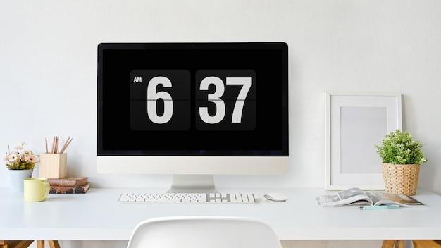 オフィスのテーブルの上の白い画面を持つモックアップコンピューター。ワークスペースと空白のスクリーンコンピューター。