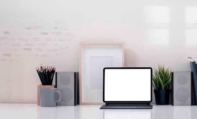 Творческое рабочее пространство макета с таблеткой пустого экрана и волшебной клавиатурой на белом столе.