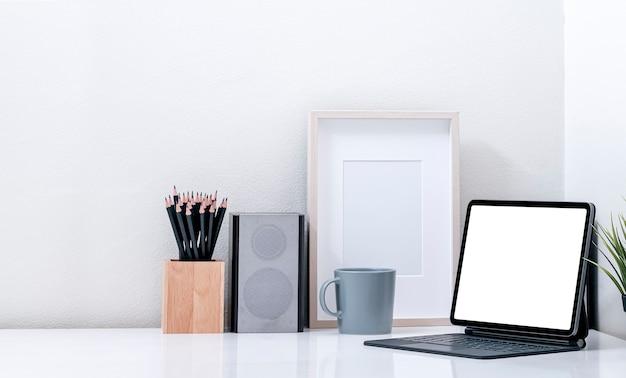 빈 화면 태블릿 및 흰색 테이블에 매직 키보드와 모형 창조적 인 작업 공간.