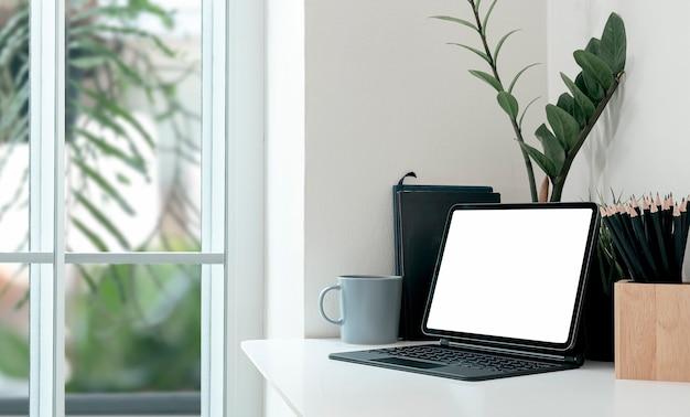Творческое рабочее пространство макета с таблеткой пустого экрана на белой верхней таблице в современной комнате.