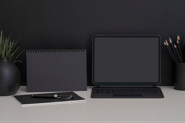 키보드와 흰색 테이블과 검정색 배경에 공급 장치가있는 태블릿이있는 모형 어두운 작업 공간.