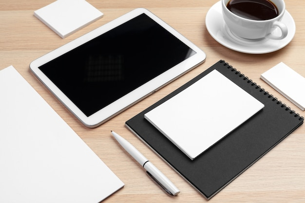 Mockup of digital tablet with notepad, supplies and coffee cup on desktop.