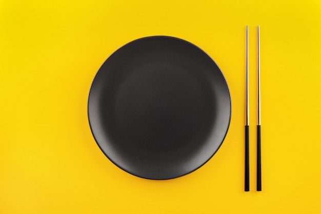 Mockup empty black round plate with gilded chopsticks flat lay on yellow background with copy space.
