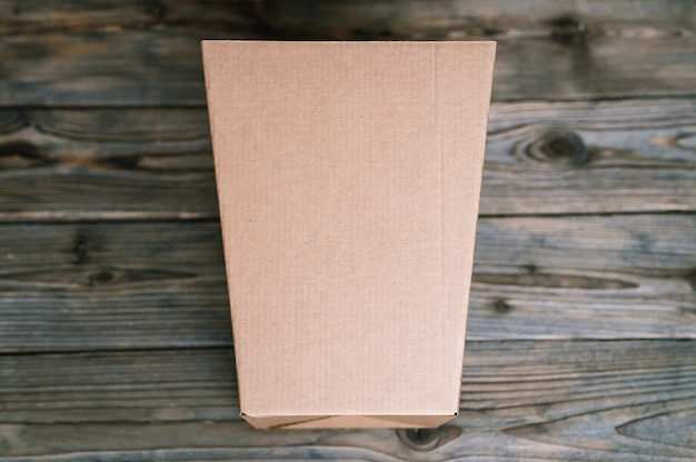 Mockup empty craft brown trapezoidal cardboard box on an old wooden table close up. top view, flat lay and space for text