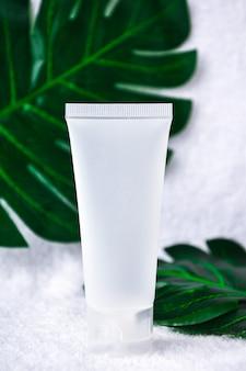 Мокап пустой белый тюбик органического натурального продукта для ухода за кожей лица на мягкой мятой белой ткани, украшенный размытым monstera deliciosa. косметический продукт с фактором spf. копировать пространство