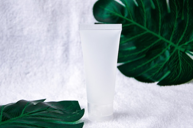 Mockup empty facial skincare organic natural product white tube on soft crumpled white cloth decoration with blurred monstera deliciosa. beauty product with spf factor. copy space