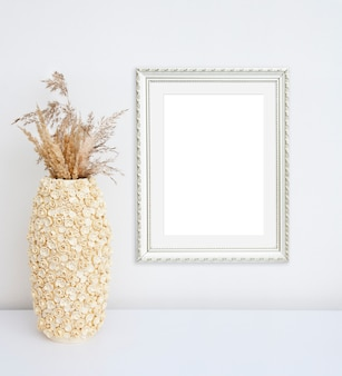 Mockup empty photo frame and beige vase with fly flowers