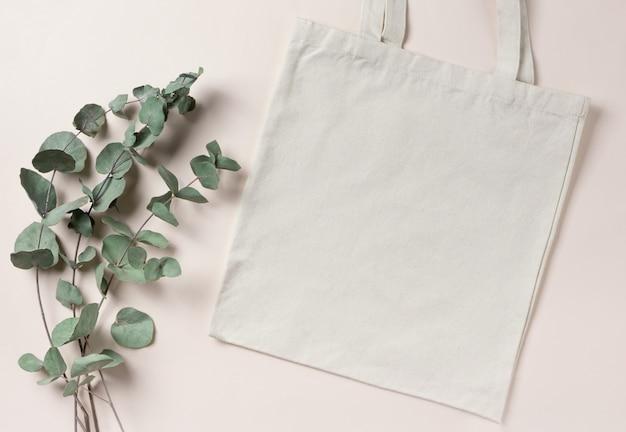 Пустой шаблон макета белая кремовая хозяйственная сумка для вашего дизайна, экологически чистая, без отходов с копией пространства. ветки эвкалипта. плоская планировка.