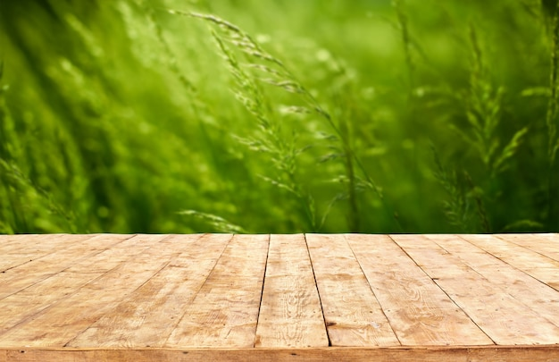 Mockup. empty wooden deck table with foliage bokeh background.
