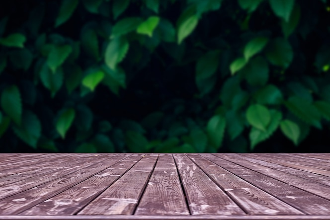 Mockup. empty wooden deck table with foliage bokeh space.