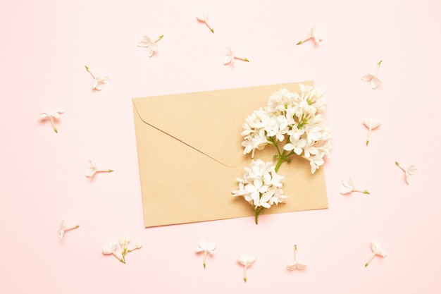 Mockup envelope with branches of lilac on a pink background