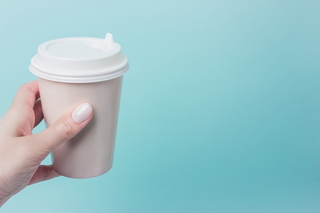 Mockup of female hand holding a coffee paper cup isolated