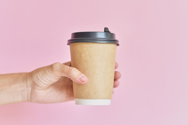 Mockup of female hand holding coffee paper cup on pink background.