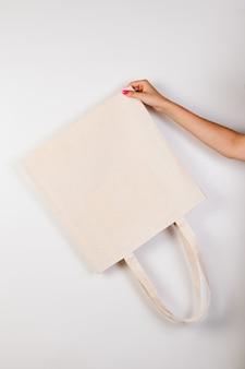 아름다운 매니큐어가 있는 흉내낸 여성 손에는 재활용 재료로 만든 거꾸로 된 흰색 에코백이 있습니다.