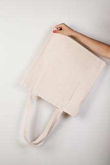 Мокап женская рука с красивым маникюром держит перевернутый белый экосумку из переработанных материалов на ...
