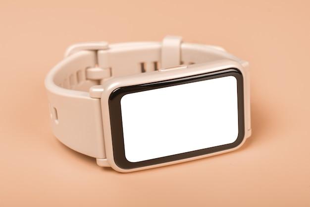 パステルカラーの背景にモックアップフィットネス時計。閉じる。ピンクのスマートウォッチの正面図