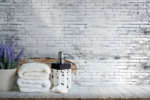 Mockup folded towel with soap and houseplant on wooden table with old brick wall