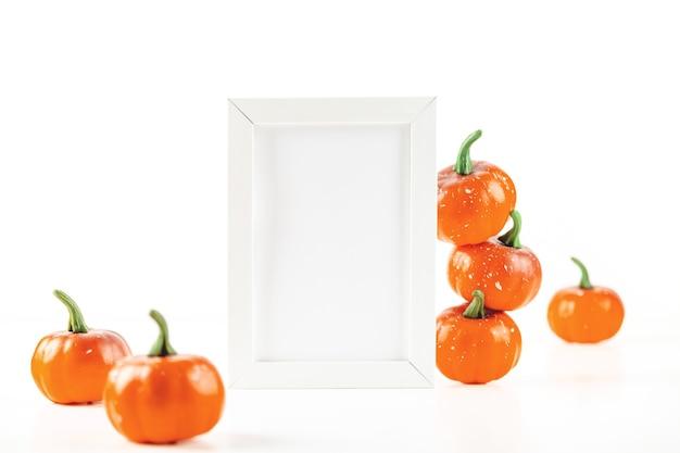 Мокап для осеннего приглашения или дизайн в белой рамке рядом с оранжевыми маленькими тыквами на белом ...
