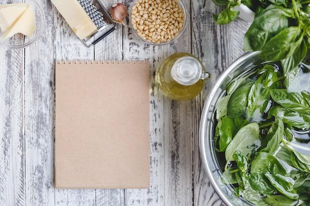 Мокап рецепта соуса песто с ингредиентами сырные орехи оливковое масло базилик на деревянном столе