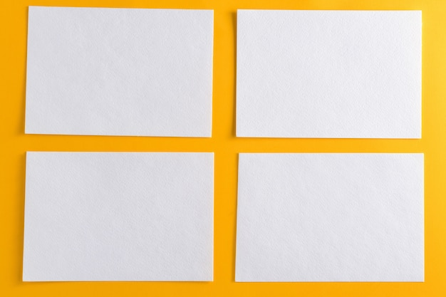 Mockup of four white business cards on yellow design paper background