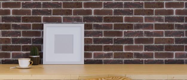 Плакат с рамкой-макетом для отображения вашего произведения искусства на деревянном столе с пустым пространством над красной кирпичной стеной
