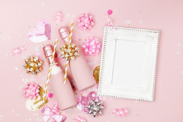 Рамка-макет с бутылками шампанского, конфетти и украшениями. день святого валентина или тема концепции вечеринки по случаю дня рождения. плоская планировка, вид сверху