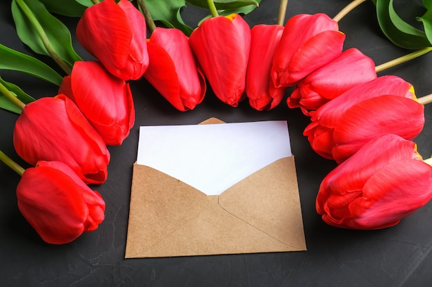 Mockup of fresh red tulips bouquet and blank greeting card in kraft envelope