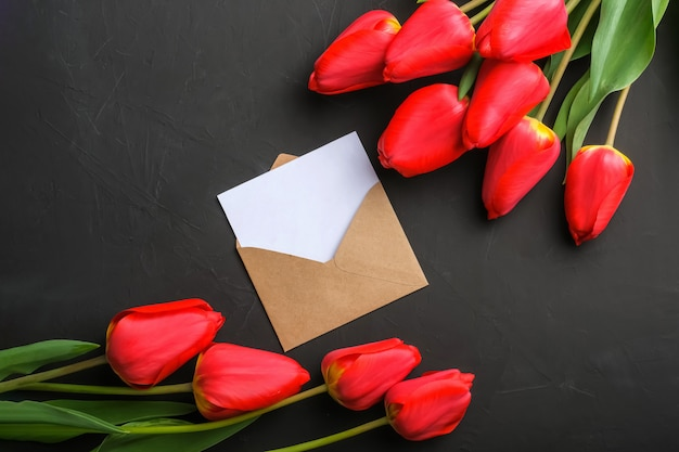 Mockup of fresh red tulips bouquet and empty greeting card in kraft envelope