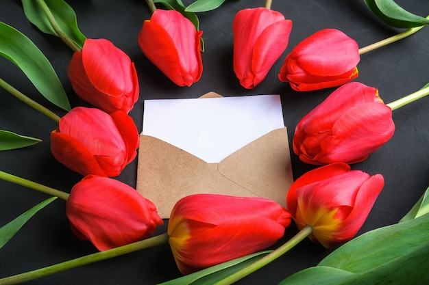 Mockup of fresh red tulips bouquet and greeting card in kraft envelope