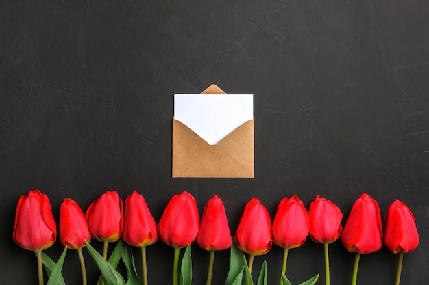Mockup of fresh red tulips bouquet in the row and greeting card in kraft envelope