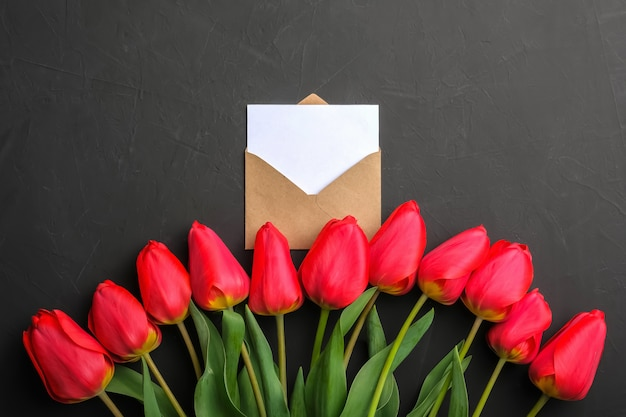 Mockup of fresh red tulips bouquet and white empty greeting card in kraft envelope