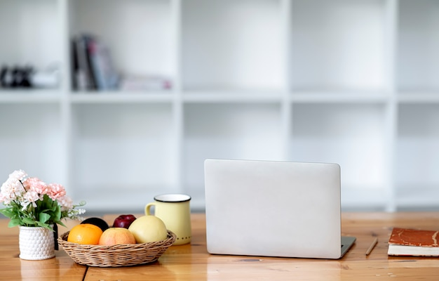 モックアップの果物とテーブルの上のノートパソコン。