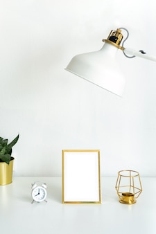 Mockup gold photo frame on white table, indoor flower, white alarm clock, gold candlestick and white lamp.