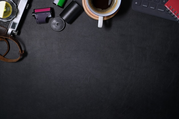 Mockup hipster leather dark desk vintage camera with creative supplies and copy space