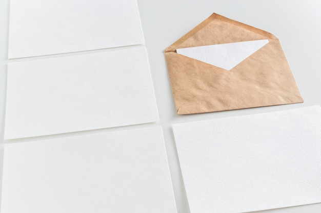 Mockup of horizontal business cards and craft envelope at white background.