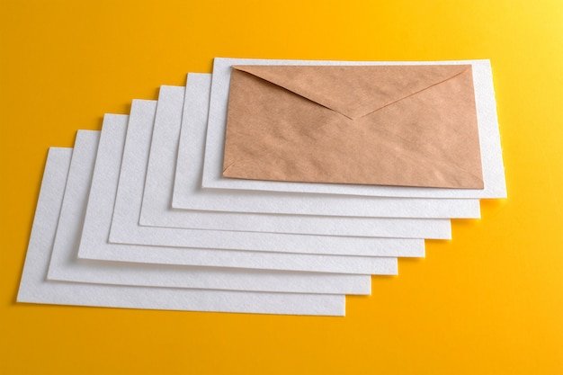Mockup of horizontal textured business cards stacks arranged in rows and crafted envelope