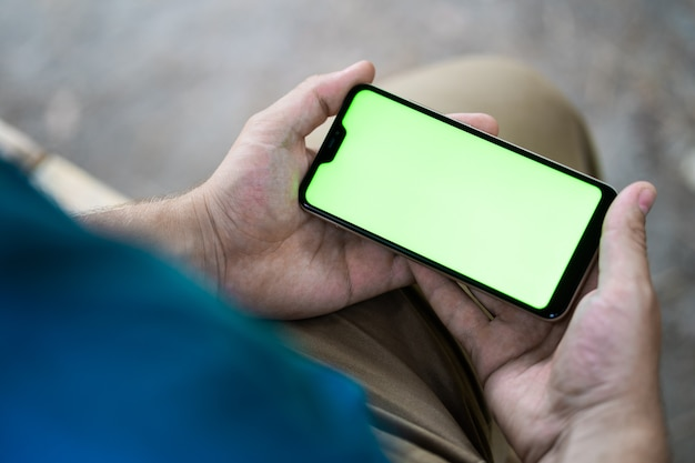 Макет изображения пустой белый экран сотового телефона. человек рука текстовые сообщения с помощью мобильного телефона на столе в кафе