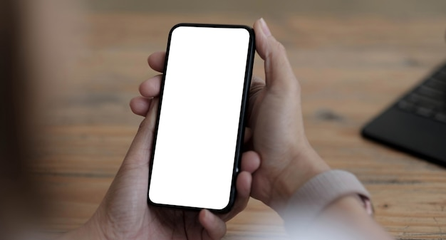 Mockup image blank white screen cell phone.women hand holding texting using mobile on desk at home office.