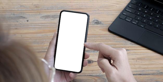 モックアップ画像空白の白い画面の携帯電話。ホームオフィスの机の上でモバイルを使用してテキストメッセージを持っている女性の手。