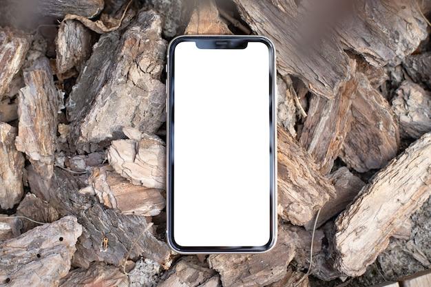 Макет изображения пустой белый экран современный сотовый телефон на открытом воздухе на фоне сосновой коры. фон пустое место для рекламного текста
