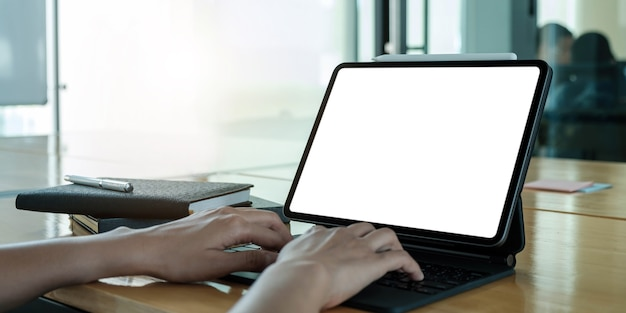 Mockup image of business woman using and typing on laptop with blank white screen and coffee cup on glass table in modern loft cafe