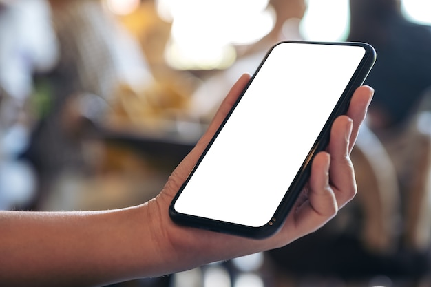 Mockup image of a hand holding black mobile phone with blank white desktop screen in cafe