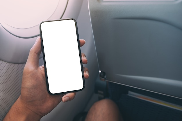 Mockup image of a hand holding a black smart phone with blank desktop screen next to an airplane window