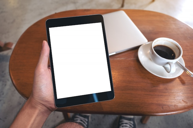Mockup image of hand holding black tablet pc with blank desktop white screen with laptop and coffee cup on wooden table